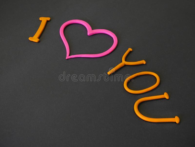 I love you inscription from plasticine with pink heart. On grey background royalty free stock photo