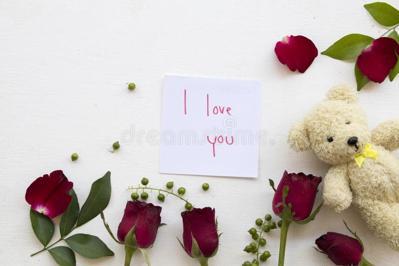 I love you message card handwriting postcard send to special. I love you message card handwriting with red rose ,teddy bear decoration flat lay style postcard stock photo
