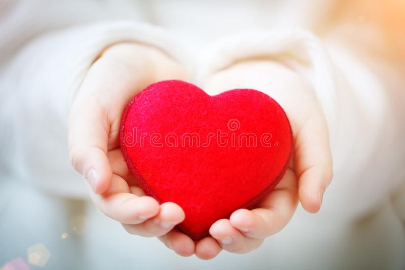 I love you Mom, Mother`s Day. Red heart in hands of the little girl. Symbol of love and family. stock photography