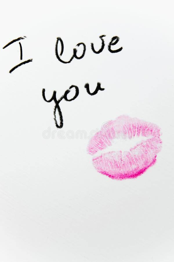 `I love you` text with lipstick kiss on white background royalty free stock image
