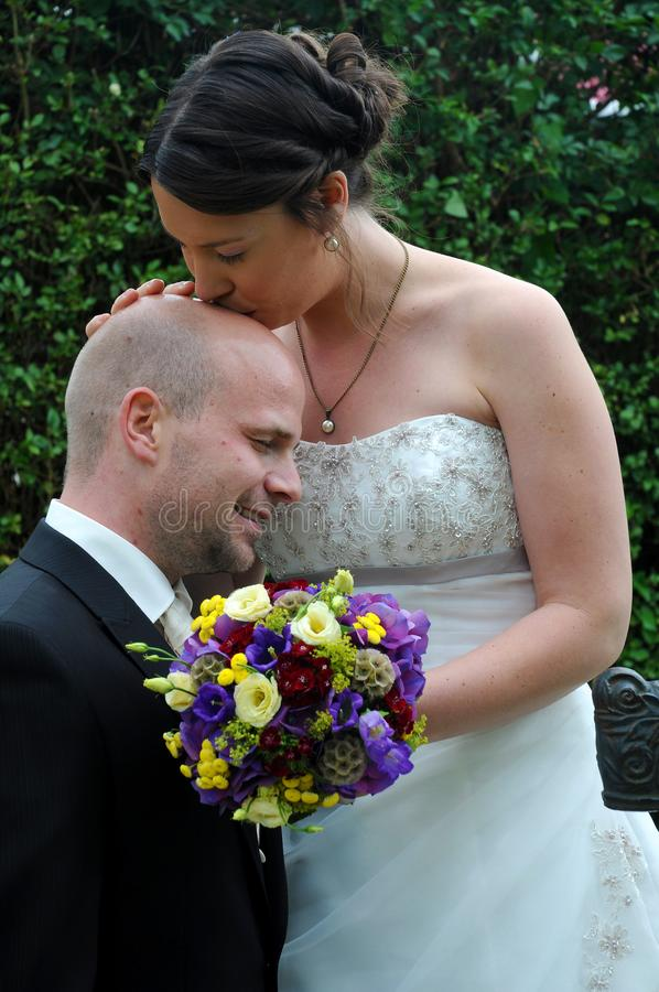 I love your bald head. Bride gives a kiss on the bald head to the bridegroom