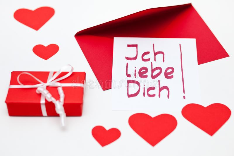 I-lovey-you-note in German for Valentine`s Day and a red parcel. stock image