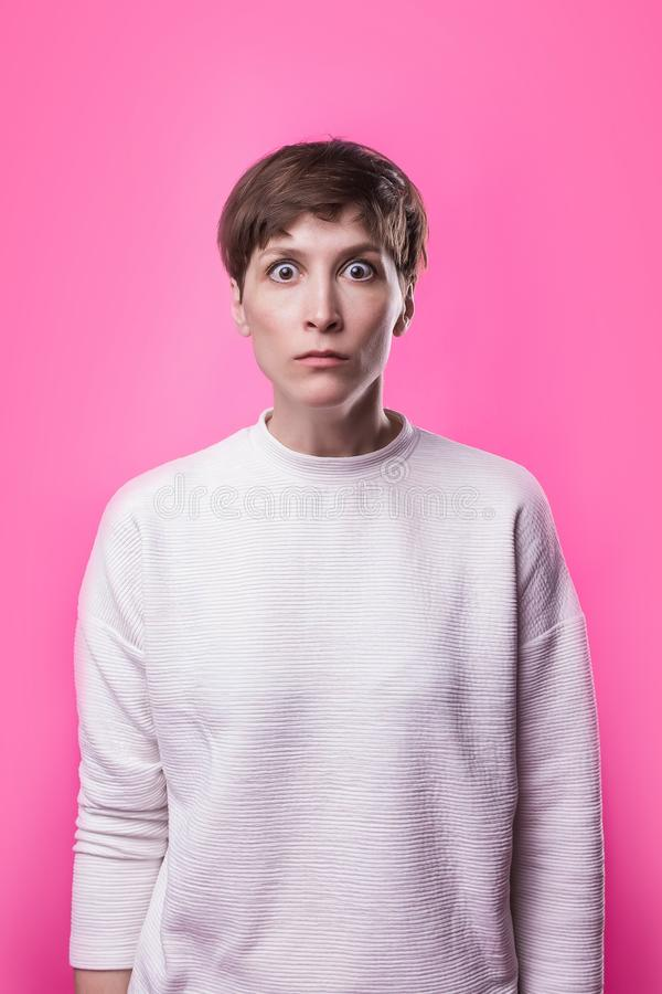 I`m afraid. Fright. Portrait of the scared woman. Business woman standing. Isolated on trendy pink studio background. Female half-length portrait. Human royalty free stock images
