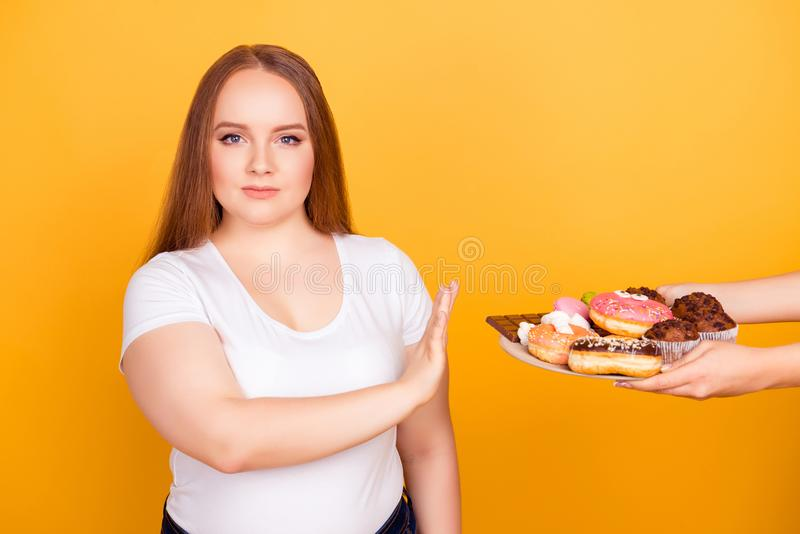 I`m against eating products containing fat! Will-powered woman w. Earing white tshirt is refusing to consume tasty delicious sweets on a plate, isolated on royalty free stock photography