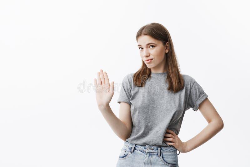 I ` m die het gaan niet bespreken Portret van knap zeker Kaukasisch meisje die met bruin haar met hand gesticuleren stock foto