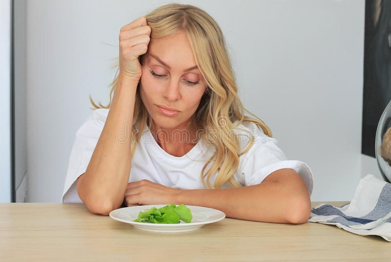 I`m fed up with untasty disgusting salad. Close up unhappy grimacing sad upset lady looking down at plate of lettuce on table stock image