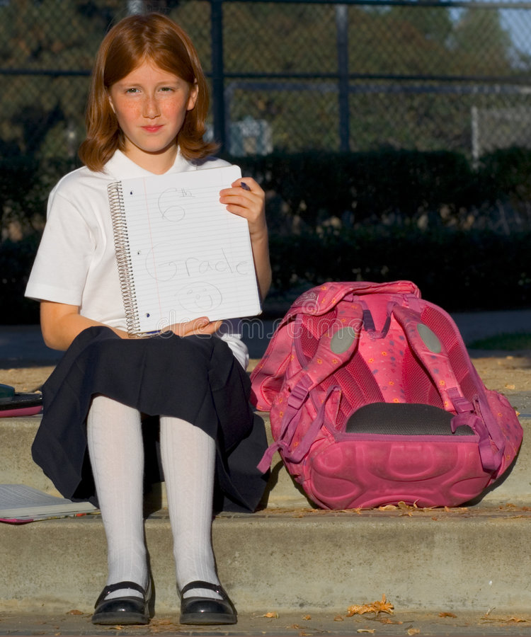 I'm from sixth grade. Girl holding sheet of paper with text 6th grade stock photography