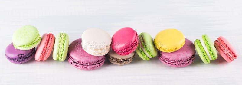 I maccheroni dei biscotti dei colori differenti si trovano in una fila lunga fotografia stock libera da diritti
