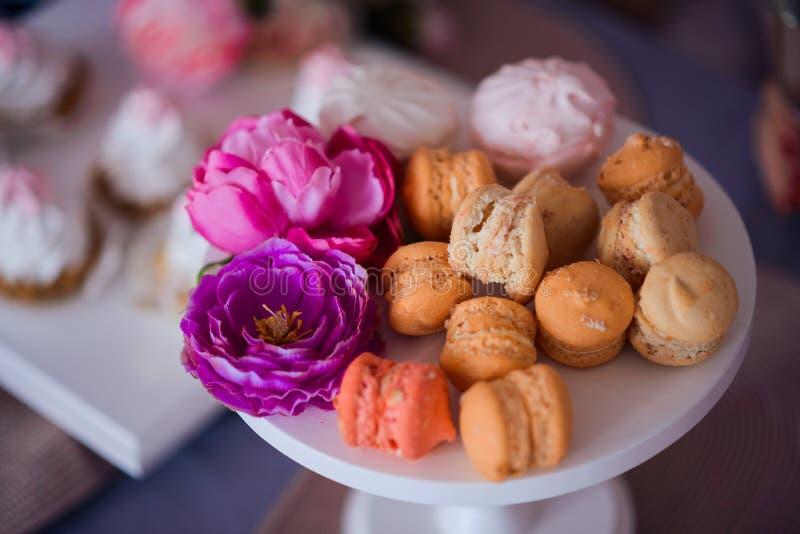 I maccheroni e le caramelle gommosa e molle stanno mettendo sul supporto del dolce, sui precedenti là sono biscotti fotografie stock
