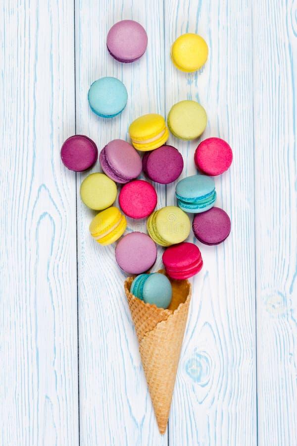 I maccheroni francesi dolci e variopinti si sono sbriciolati dal cono della cialda immagini stock libere da diritti