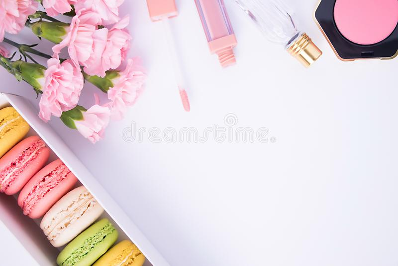 I maccheroni variopinti, profumo, arrossiscono, rossetto e fiori rosa del garofano su un fondo bianco Isolato Il concetto della p fotografie stock