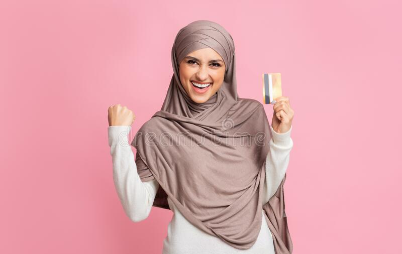 Happy islamic woman in hijab celebrating success with gold credit card stock image