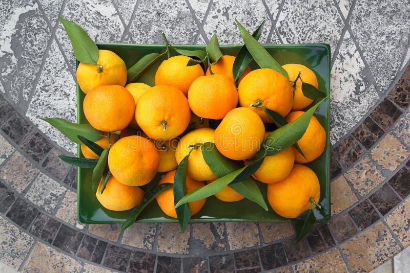 I mandarini freschi si trovano sulla tavola a mosaico di pietra nella piastra verde, vista dall'alto immagini stock libere da diritti