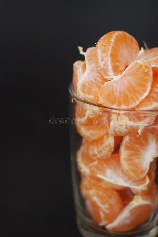 I mandarini sbucciati freschi si sono divisi nelle fette sulla tazza di vetro Proprietà dei mandarini per il concetto di salute s fotografie stock