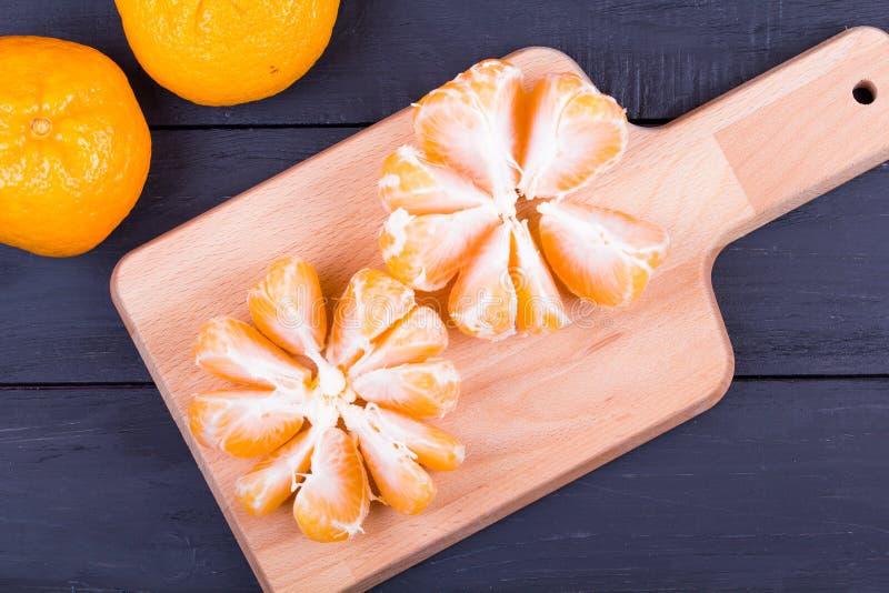 I mandarini sbucciati su un tagliere immagine stock