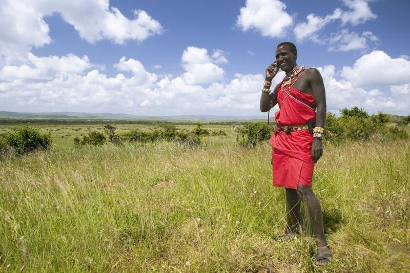 I masai in toga rossa parlano sul suo telefono cellulare dai pascoli della tutela della fauna selvatica di Lewa nel Kenya del nor fotografie stock