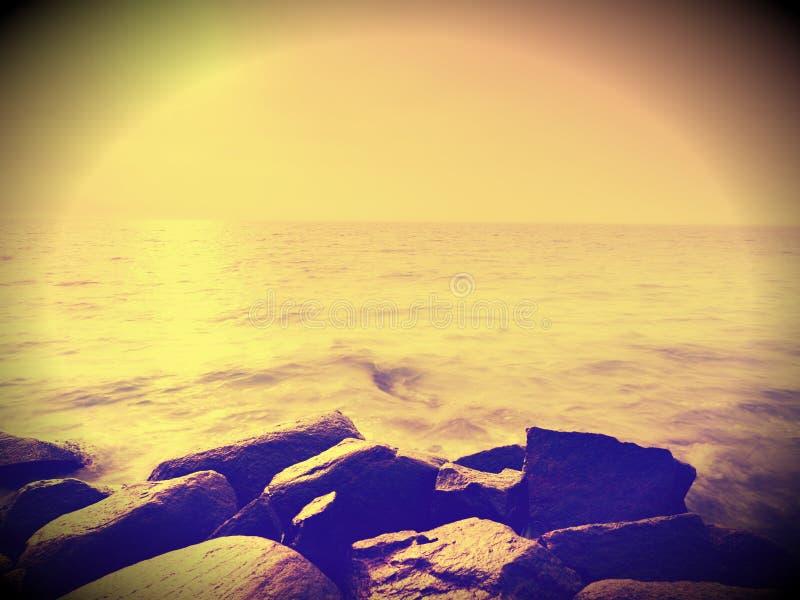 I massi alla riva dell'isola attaccano su dal mare liscio La costa pietrosa sfida alle onde dell'oceano immagine stock libera da diritti