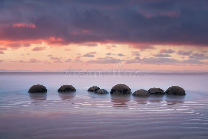 I massi di Moeraki sul Koekohe tirano, costa orientale della Nuova Zelanda Tramonto ed esposizione lunga e un cielo drammatico di fotografia stock libera da diritti
