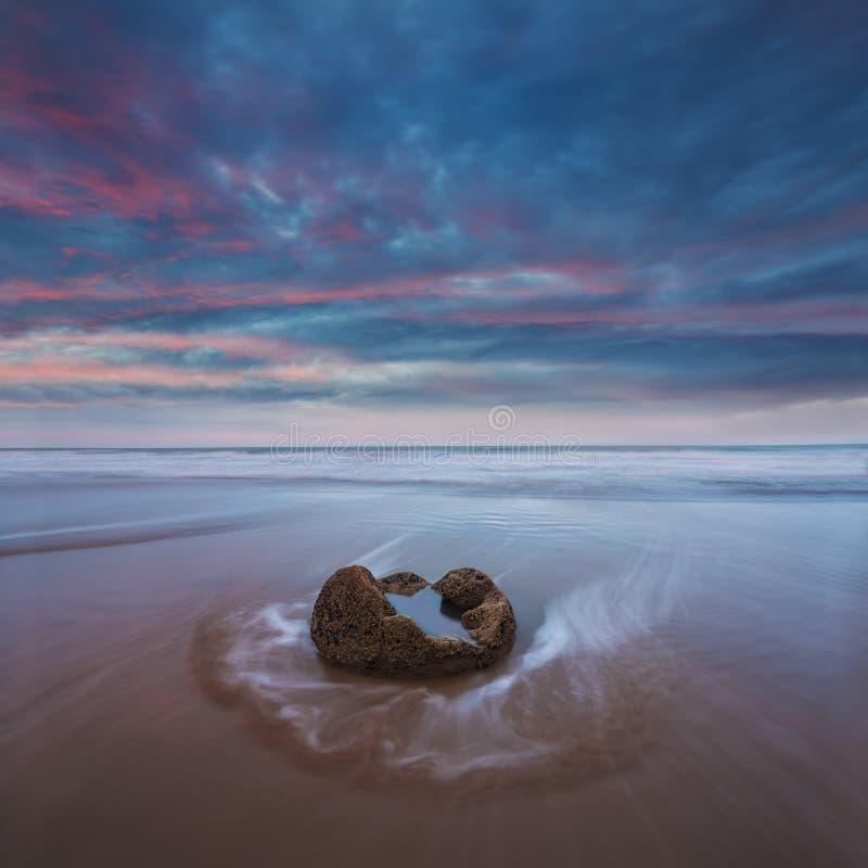 I massi di Moeraki sul Koekohe tirano, costa orientale della Nuova Zelanda Tramonto ed esposizione lunga e un cielo drammatico di fotografie stock libere da diritti