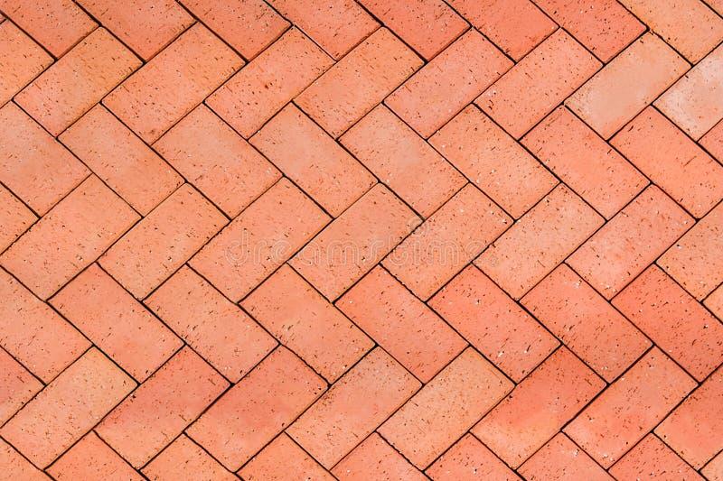 I mattoni Rosso-arancio hanno piastrellato il pavimento con il fondo di struttura del modello di zigzag immagine stock libera da diritti