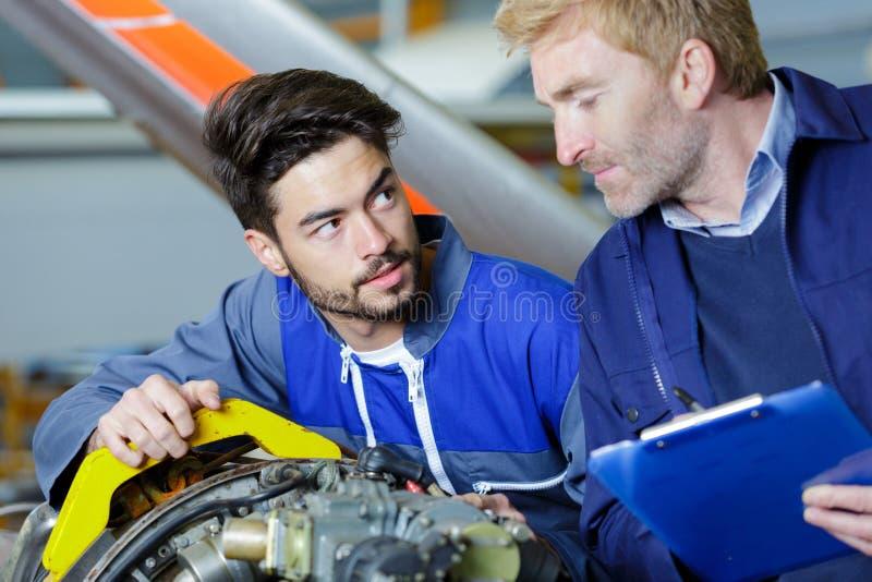 I meccanici controllano la parte del veicolo nell'officina del meccanico immagine stock