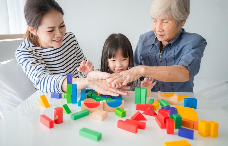 I membri femminili di diverse generazioni dei cubi di legno di un gioco della famiglia colorano la scala geometrica insieme alla  immagine stock
