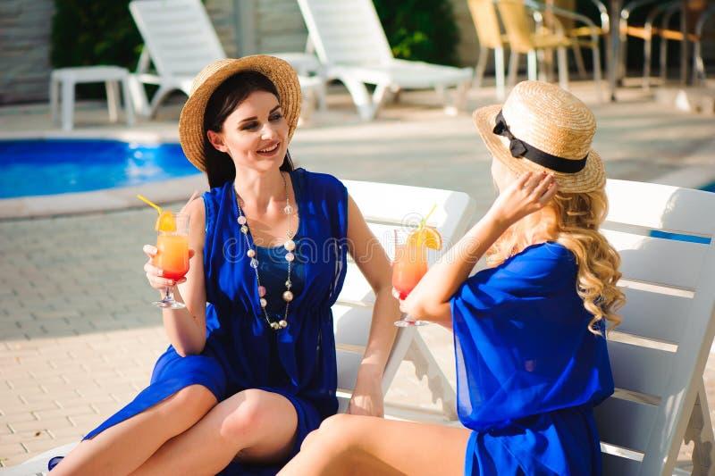 I migliori amici felici delle ragazze sulla festa di stupore, beve i cocktail vicino allo stagno ed a divertiresi fotografia stock
