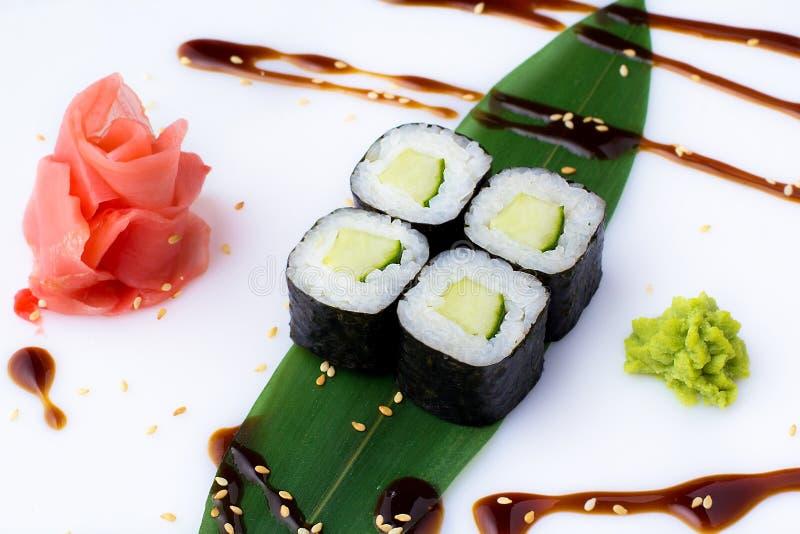 I mini-rotoli freschi deliziosi con il cetriolo su una banana coprono di foglie Rotoli di sushi su un fondo bianco con lo zenzero fotografie stock libere da diritti