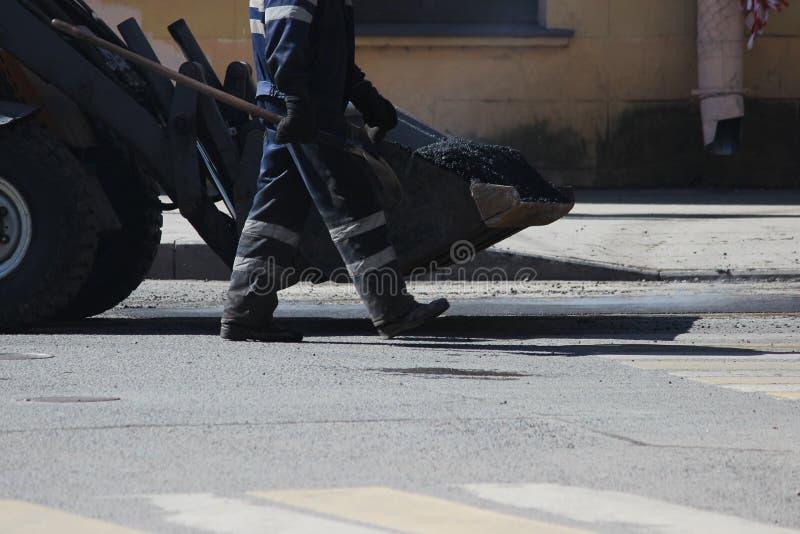 I mini trasporti dell'escavatore nel mestolo asfaltano le briciole per riparare i pozzi della strada nella città di St Petersburg immagini stock libere da diritti