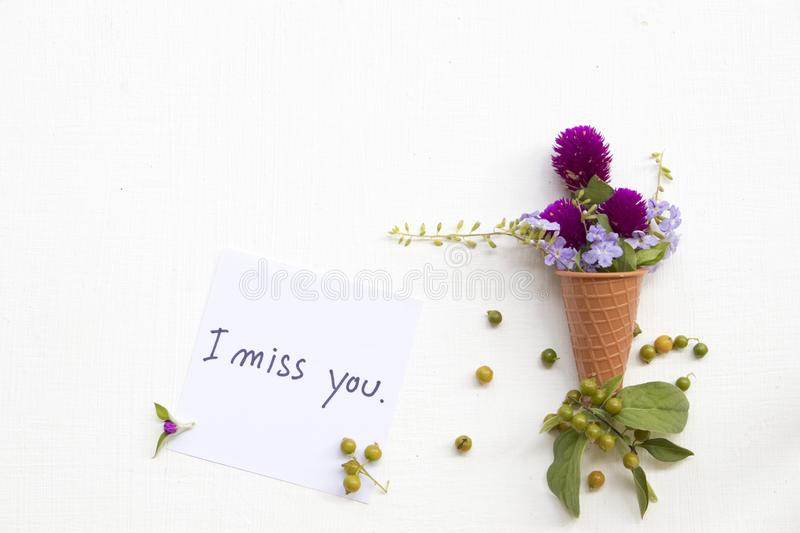 I miss you  message card handwriting with purple flower amaranth in cone royalty free stock photo