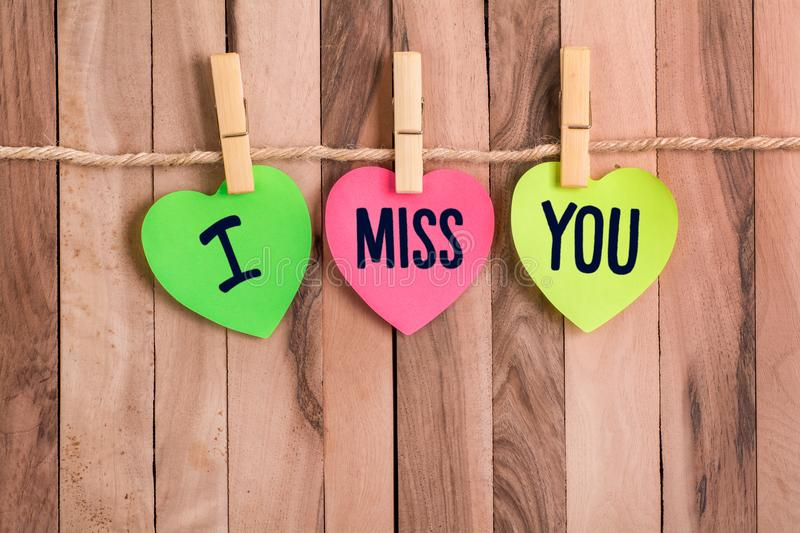 I miss you heart shaped note. I miss you text in color heart shaped note with clothespin and rope on wooden background royalty free stock image