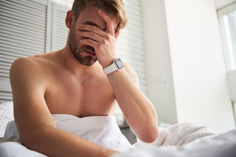 Young sleepy man waking up in morning. I missed my meeting. Frustrated male oversleeping at home. He is sitting on bed and rubbing face in disappointment royalty free stock photo