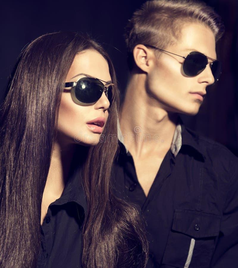 I modelli di moda coppia gli occhiali da sole d'uso fotografia stock libera da diritti