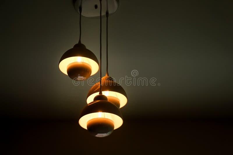 I modelli di tre lampade leggere moderne che appendono sul fondo del soffitto fotografia stock