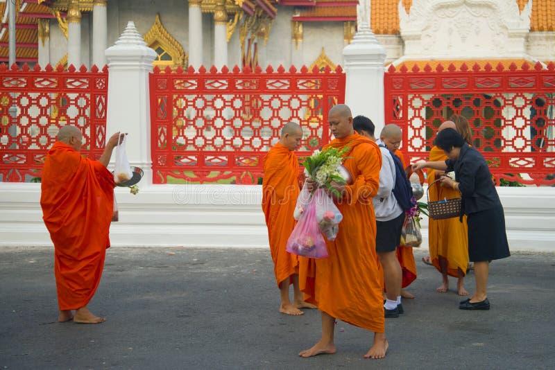 I monaci buddisti del tempio di Wat Benchamabophit accettano i regali, primo mattino Bangkok, Tailandia fotografie stock libere da diritti