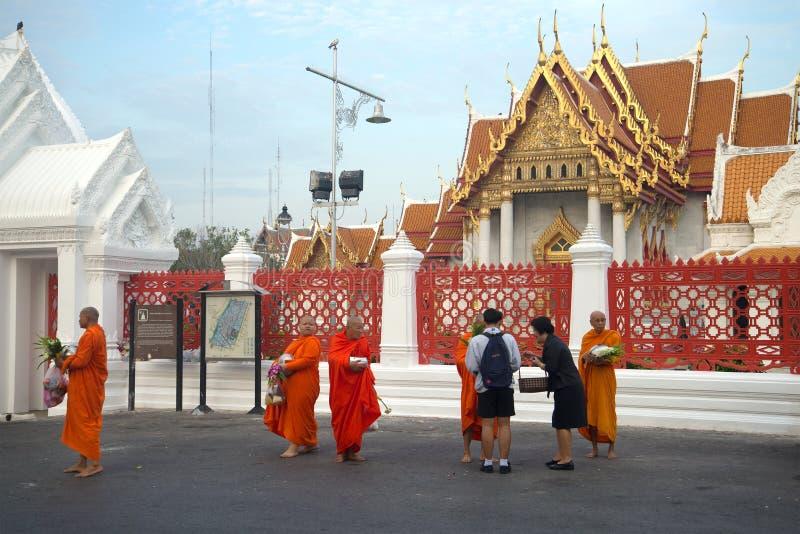 I monaci buddisti del tempio di Wat Benchamabophit riuniscono l'alimento nelle prime ore del mattino, Bangkok fotografia stock libera da diritti