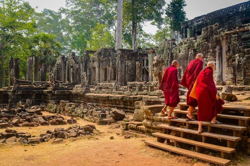 I monaci buddisti entrano nel tempio di Bayon a Angkor Wat, Siem Reap, Cambogia fotografia stock libera da diritti