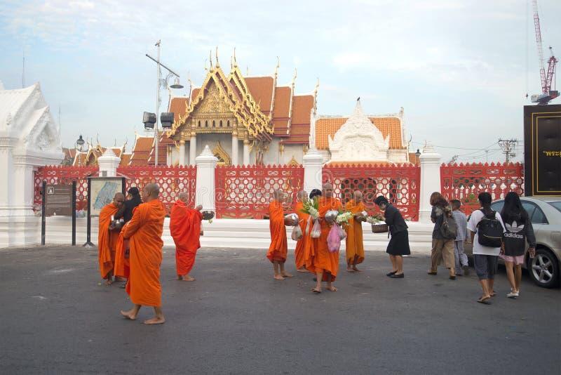 I monaci buddisti raccolgono l'alimento e le offerti al tempio Wat Benchamabophit nel primo mattino Bangkok, Tailandia fotografia stock libera da diritti