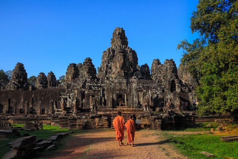 I monaci nei fronti di pietra antichi del tempio di Bayon, Cambogia fotografia stock libera da diritti