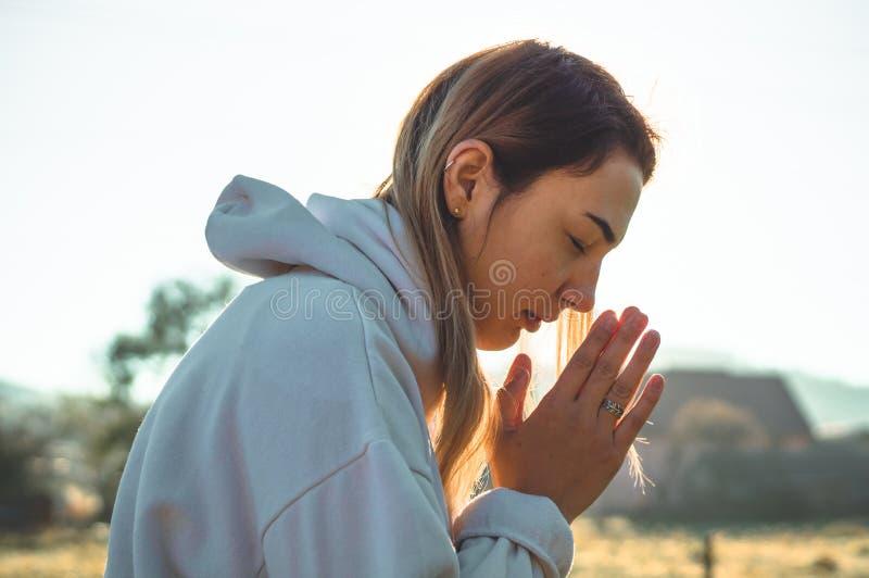 I morgon stängde flickan henne ögon som utomhus ber, händer vikta i bönbegreppet för tro, andlighet, religionbegrepp royaltyfria foton