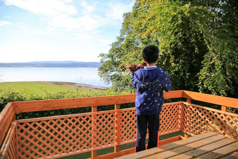 I morgonen lite spelade pojken fiolen på sjösidan arkivbild