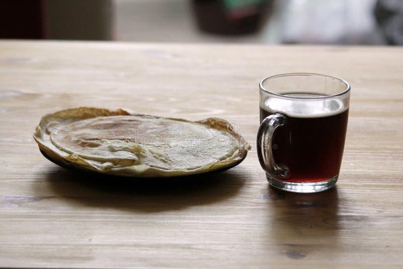 I morgonen på tabellen en kopp kaffe och en platta av pannkakor royaltyfri foto