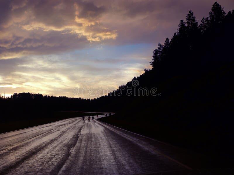 I motociclisti di Black Hills guidano al tramonto sulla strada bagnata immagine stock