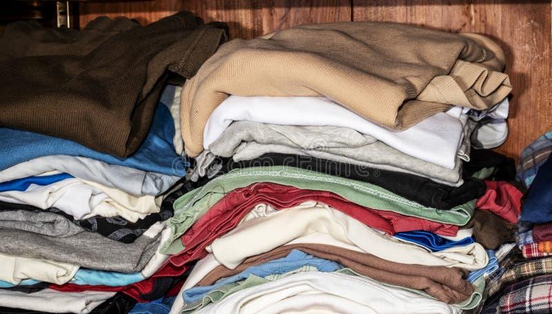 I mucchi dei vestiti degli uomini hanno piegato sugli scaffali fotografie stock libere da diritti