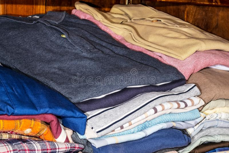 I mucchi dei vestiti degli uomini hanno piegato sugli scaffali immagini stock libere da diritti