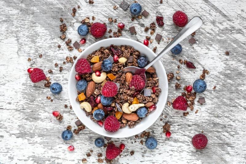 I muesli del cioccolato o il granola casalinghi in una ciotola con un cucchiaio, bacche, hanno asciugato i frutti ed i dadi fotografia stock libera da diritti