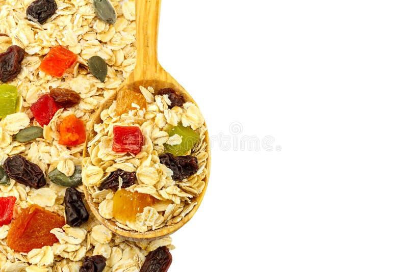 I muesli o l'avena del cereale si sfaldano con frutta secca, il cucchiaio di legno, studio isolato con spazio per testo fotografie stock