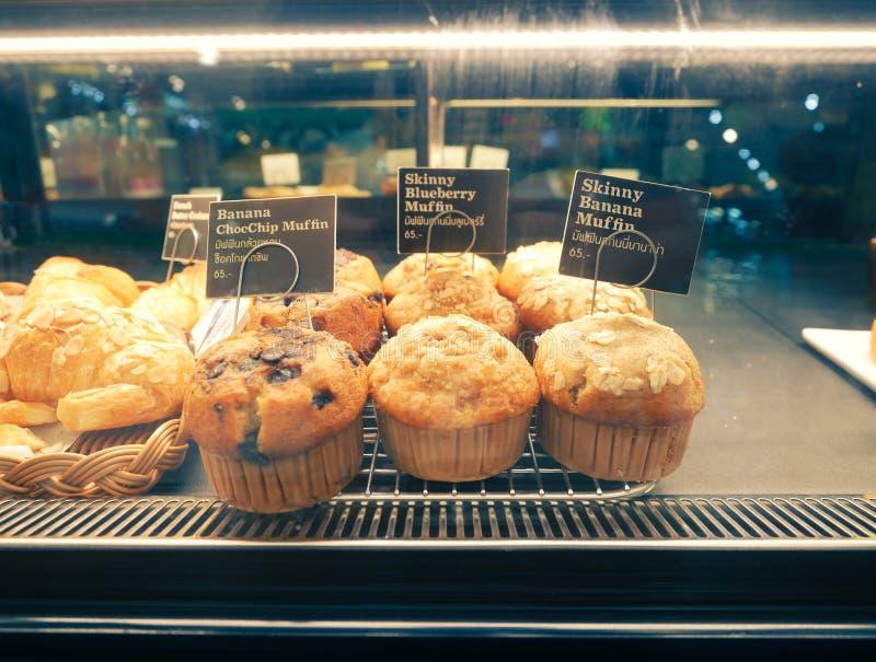 I muffin della banana e del cioccolato nel supporto di carta del bigné sui dessert dell'esposizione di vendita al dettaglio del v fotografia stock
