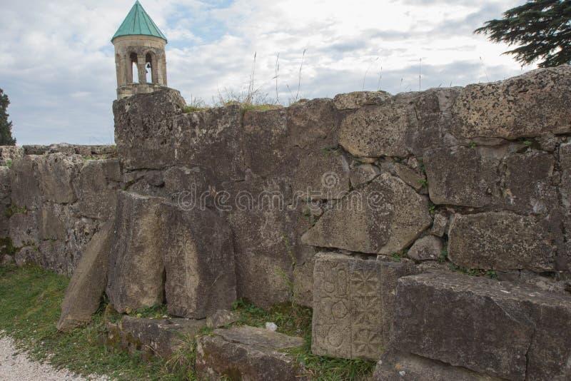 I mura di cinta rotti della città georgiana antica Iscrizioni antiche scolpite nella pietra fotografia stock
