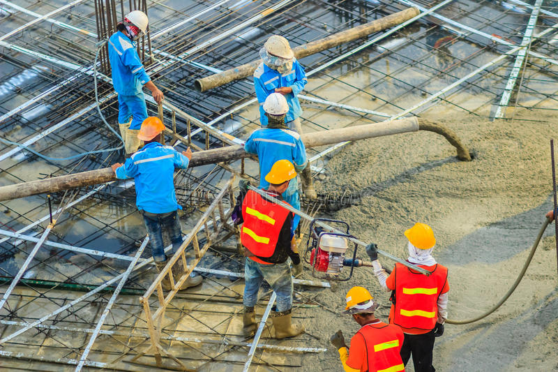 I muratori che per mezzo di un motore a benzina del vibratore per calcestruzzo scrivono al cantiere per comprimere il calcestruzz fotografia stock libera da diritti